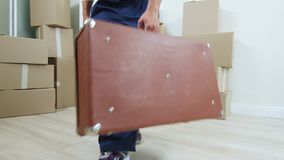 Loader carries old large brown case into room with boxes. Loader in blue uniform carries old large brown case into room with packed boxes when moving to new stock video