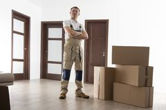 Loader with cardboard boxes in apartment. Mover at house. Relocation services man. stock images
