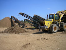 Loader and crusher at gravel pit. Loader with crusher in background at gravel pit stock image