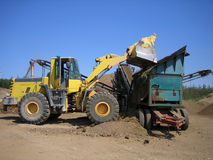 Loader and crusher at gravel pit Stock Photography