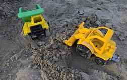 Loader and dumper. Toy loader and dumper working in the sand at seaside Stock Photo
