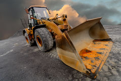 Loader excavator. Image of a quarry Loader / excavator with a dramtic sky background Royalty Free Stock Photo