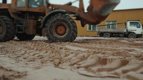 Loader excavator machine loading dumper truck at sand quarry, new factory building stock video footage