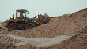 Loader excavator machine loading dumper truck at sand quarry, new factory building stock video