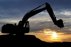 Loader excavator over sunset. Silhouette of Excavator loader at construction site with raised bucket over sunset Stock Photo