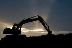 Loader excavator silhouette. Silhouette of loader excavator scoop shovel over scenic sunset Stock Image