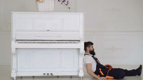 Loader lean on piano instrument. Man with beard, worker in overalls and helmet fall asleep tired, white background. Courier fall asleep while moving furniture stock footage