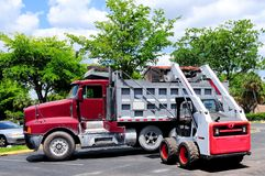 Loader loading truck in parking lot Stock Images
