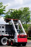 Loader loading truck in South Florida parking lot Royalty Free Stock Images
