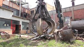 Loader manipulator with hydraulic grappling claw is collecting scrap metal. Gripper machine catch scrap with hydraulic crab claw wile worker is cutting old metal stock video