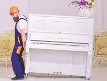 Loader moves piano instrument. Courier delivers furniture in case of move out, relocation. Man with beard, worker in. Overalls and helmet lifts up piano, white royalty free stock photos