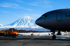 Loader pulls up to the plane on the tarmac. At the background of high snowy mountains Royalty Free Stock Photo