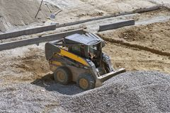 Loader small bulldozer moving breakstone at construction area Royalty Free Stock Photo