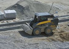Loader small bulldozer moving breakstone at construction area royalty free stock photography