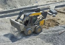 Loader small bulldozer moving breakstone at construction area Royalty Free Stock Photos