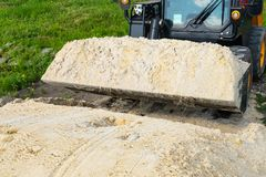 The loader took the sand into the bucket for construction work. Copy paste royalty free stock photos