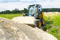 The loader took the sand into the bucket for construction work. Copy paste royalty free stock image