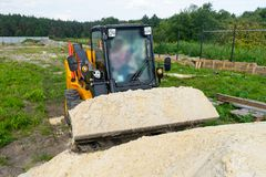 The loader took the sand into the bucket for construction work. Copy paste royalty free stock photo