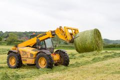 Loader tractor moving a round bale from field Royalty Free Stock Photography