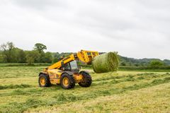 Loader tractor moving a round bale from field Royalty Free Stock Photos