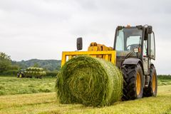 Loader tractor moving a round bale from field Stock Images
