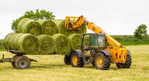 Loader tractor moving a round bale from field Royalty Free Stock Photo