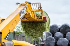 Loader tractor stacking round bales in a stack Stock Photography