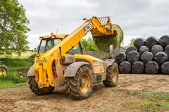 Loader tractor stacking round bales in a stack Royalty Free Stock Image