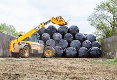 Loader tractor stacking round bales in a stack Stock Photo