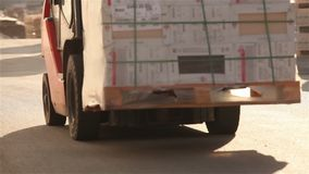 The loader transports cargo in a warehouse, a loader in a warehouse, a warehouse of a large enterprise, industrial. The loader will load the load on the skald stock video footage