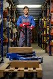 Loader using hand pallet truck Stock Photos