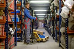 Loader using hand pallet truck. In a warehouse Royalty Free Stock Images