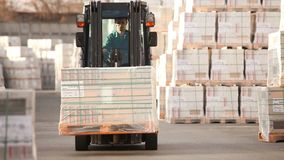 The loader transports cargo in a warehouse, a loader in a warehouse, a warehouse of a large enterprise, industrial. The loader will load the load on the skald stock footage