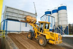 Loader works at concrete plant. Front-end loader loading with sand bunker of Stationary Concrete Batching Plant stock photo