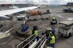 Loaders at the airport unload baggage from the aircraft. FRANKFURT, GERMANY - September 12, 2017 Loaders at the airport unload baggage from the aircraft Stock Images