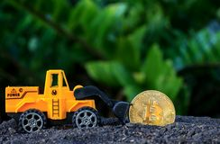Loaders golden bitcoin. Loaders golden bitcoin from the soil Royalty Free Stock Image