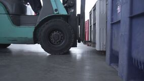 Loaders lift big plastic box in warehouse logistics center