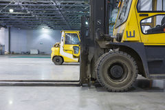 Loaders in modern storehouse. Two loaders in modern storehouse Royalty Free Stock Photos