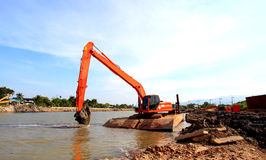 Loaders working in the middle of the river. Stock Image