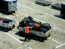 Loading aircraft passenger luggage. Worker loading aircraft luggage into cart Stock Image