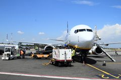 Loading airplane on airport. Loading airplane of low-cost airlines Ryanair with luggage on the runway on the airport Ciampino in Rome, Italy Royalty Free Stock Photography