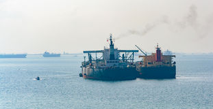 Loading anchored oil supertanker via a ship-to-ship oil transfer Stock Images