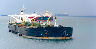 Loading anchored oil supertanker via a ship-to-ship oil transfer Royalty Free Stock Photography