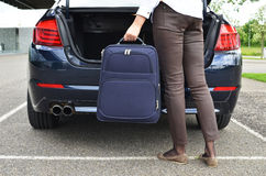 Loading a bag into the trunk. Girl loading a bag into the trunk Royalty Free Stock Photography