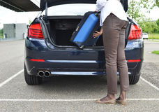 Loading a bag into the trunk. Girl loading a bag into the trunk Stock Photo