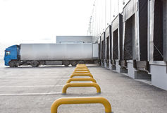 Loading big blue truck at the big distribution warehouse. With gates Royalty Free Stock Photo