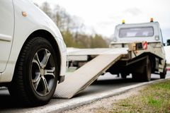 Loading broken car on a tow truck. On a roadside Stock Photos
