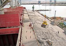 Loading cargo of cement clinker in bulk carrier by ships cranes in the port of Izmir, Turkey. royalty free stock photography