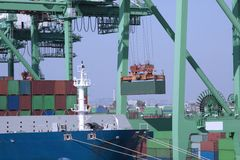 Loading cargo ship. Cargo ship being loaded by crane Royalty Free Stock Photo