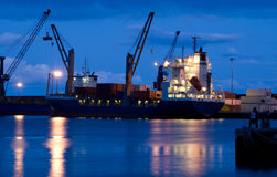 Loading cargo ship. Cranes loading a cargo ship during the night stock images